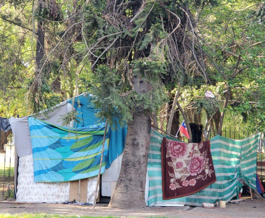 Homeless encampment against park wall